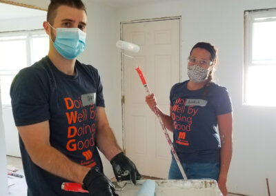 Dave Ozga and Angela Ziogas paiting at The Schuster Group Hartford Area Habitat for Humanity Build Day