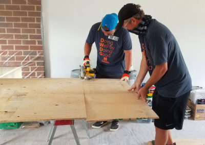 Neil Roberts and Ryan Lawless cutting wood at The Schuster Group Hartford Area Habitat for Humanity Build Day