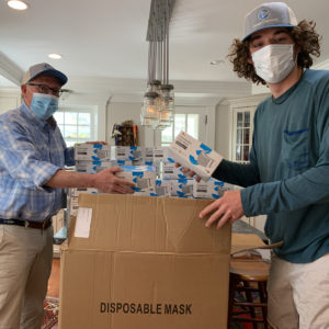 Rollin Schuster, Managing Principal of The Schuster Group, President and Founder of TANGO and his son Lars packing up PPE donations.