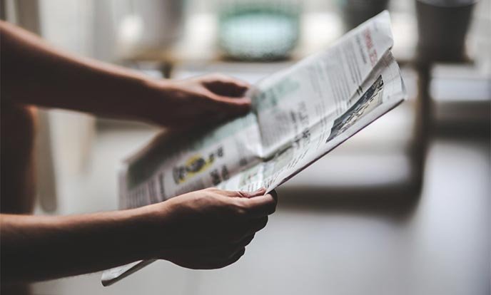 Person holding and reading a nonprofit newspaper